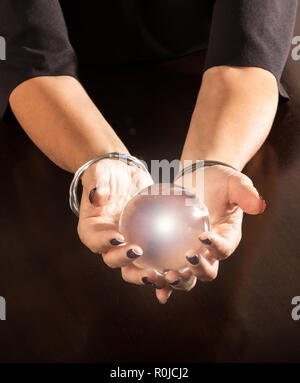 Fortune teller holding a magical glowing crystal ball cradled in her hands over a dark table with copy space below - Stock Photo