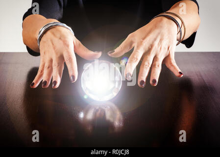 Fortune teller or soothsayer with a glowing crystal ball or sphere reflected on a shiny wooden table in a close up view of her hands