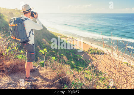 Young backpacker traveling along mountains, happy travel man explore island to Bali, discovering world, summer vacation concept - Stock Photo