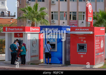People using Ziraat Bankasi, YapiKredi and Akbank ATM machines in Kemer, Turkey - Stock Photo