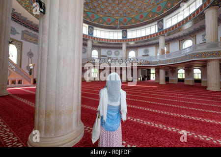 Rear view of a woman wearing a scarf on her head inside the Huzur Cami Islamic mosque in Kemer, Antalya province, Turkey - Stock Photo