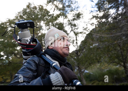 Nature wildlife professional photographer with a Canon 200-400mm f4 super tele photo zoom lens on his shoulder outdoors - Stock Photo