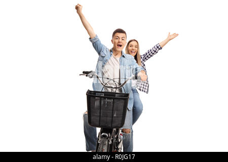 Cheerful teenage boy and girl riding on a bike and raising hands up isolated on white background - Stock Photo