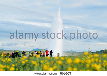 Tourists watching Strokkur geyser erupt at the popular geothermal hot springs in the Haukadalur Valley, south-west Iceland. - Stock Photo