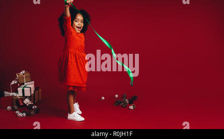 Little girl playing with a ribbon standing beside a pile of gift boxes. Smiling kid having fun playing with decorative items standing against a red ba - Stock Photo