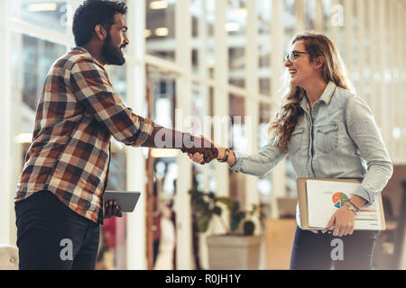Business partners shaking hands after a discussion. Woman entrepreneur holding official papers greeting a business client at work place. - Stock Photo