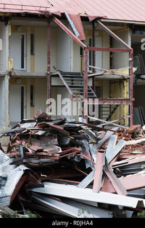 Scrap metal in front of partially demolished house. - Stock Photo