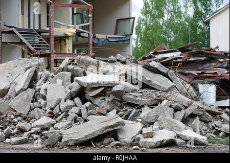 Pile of concrete in front of partially demolished house. Focus on foreground. - Stock Photo