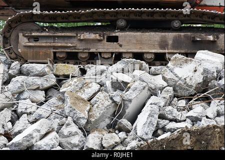 Heavy construction machine above pile of broken concrete at a building demolition site. - Stock Photo