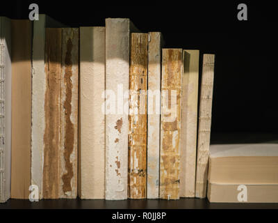 Old, worn out books standing on a black book shelf - Stock Photo