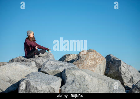 woman sitting in yoga lotus position, meditating, dressed for warmth
