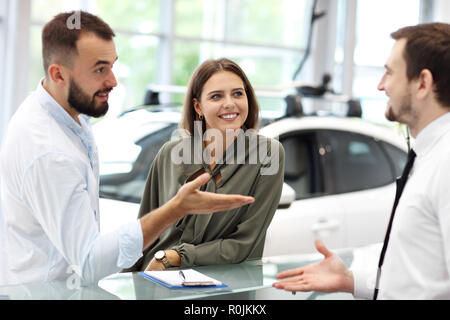 Confident young salesman explaining car features to the young attractive owners - Stock Photo