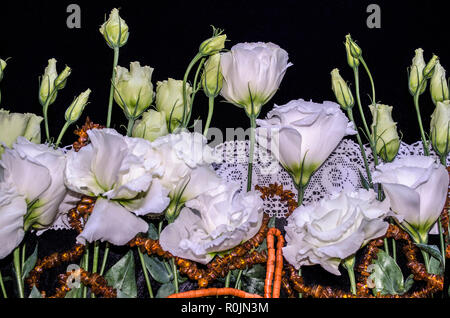 White flowers of Lisianthus with red coral and amber beads on a white openwork embroidered edging,lie the black plywood - Stock Photo