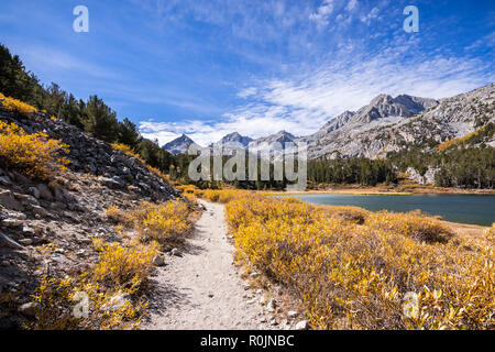 Little Lakes Valley hiking trail on a sunny fall day, following the shoreline of Long Lake in the Eastern Sierras; John Muir Wilderness; California Stock Photo