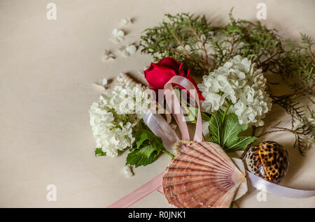 Delicate bouquet of white hydrangea with a bud of red rose on a branch of eucalyptus and sea shells on a light wooden table - Stock Photo
