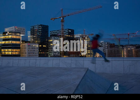 Young boy running and jumping on the rooftop of the Opera House in Oslo, Norway - just in front of the Barcode area with lots of highrise buildings. - Stock Photo