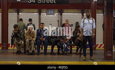 Subway riders wait on the platform for a D train at 34th Street and Broadway in Manhattan, New York City. - Stock Photo