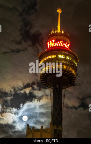 The Sydney Tower lit up at night with a full moon in the evening sky Sydney NSW Australia. - Stock Photo