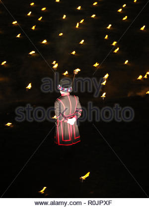 View of a Beefeater standing guard amid the thousands of torches lit to remember the WW1 Armistice Centenary at the Tower of London November 2018 - Stock Photo