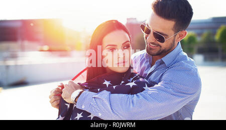 Young man covering woman with USA flag in sunset outdoors - Stock Photo