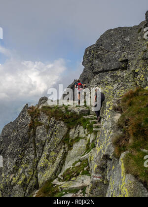 A couple hiking on a high trail in the Polish Tatra mountains