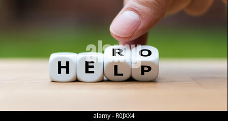 Hand is turning a dice and changes the word 'help' to 'hero' - Stock Photo