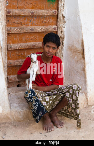 A boy sitting in front of an old wooden door holds in his arms a young goat on May 8, 2007 in Shibam, Yemen - Stock Photo