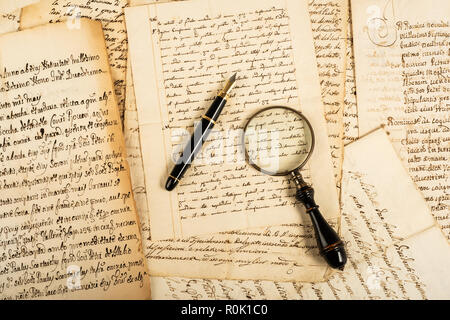 Fountain pen and magnifying glass with letters - Stock Photo