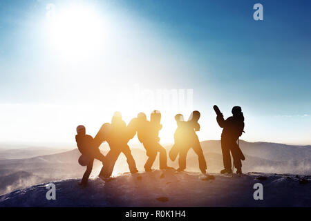 Group of happy friends skiers and snowboarders are having fun. Five silhouettes with ski and snowboards on mountain top at ski resort - Stock Photo