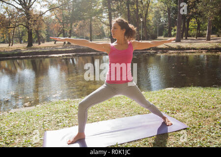 Young Woman Performing Yoga Exercise in Warrior Pose At Park Near Lake. Beautiful Morning Autumn Day. Healthy Motivation. - Stock Photo