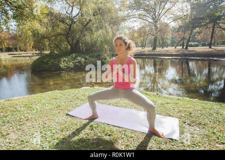 Flexible Young Woman Performing Yoga Exercise In Nature Near Water. Sporty Girl Workout Outdoor. - Stock Photo