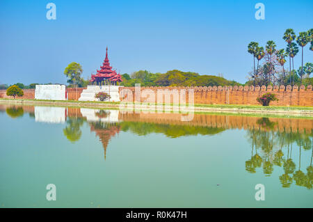 The walls with towers and lush park behind, the only elements of Royal Palace that seen from city streets, Mandalay, Myanmar - Stock Photo