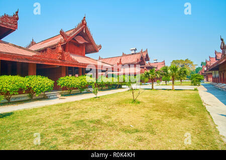 The lines of wooden buildings with pyatthat roofs on the territory of Royal Palace in Mandalay, Myanmar - Stock Photo