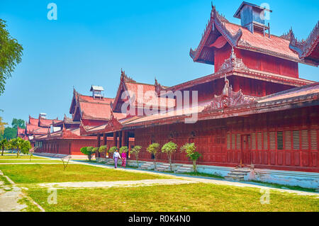 MANDALAY, MYANMAR - FEBRUARY 23, 2018:  The Burmese tourists walk along the restored timber buildings of Royal Palace, on February 23 in Mandalay - Stock Photo