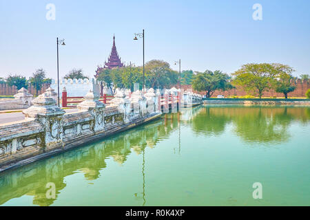 The old bridge across the moat leads to the gate of medieval citadel of Royal Palace, Mandalay, Myanmar. - Stock Photo