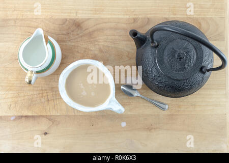 Top view of Black cast iron tea pot with warm cup of tea and pitcher of cream and spoon on a wooden table or tray. - Stock Photo