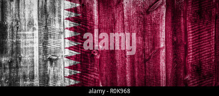 National flag of Qatar on a textured wooden background, fence or wall - Stock Photo