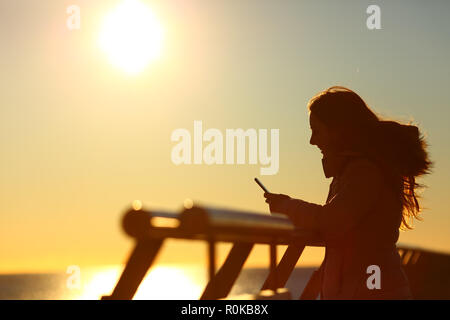 Side view portrait of a woman silhouette using a smart phone at sunset on the beach - Stock Photo