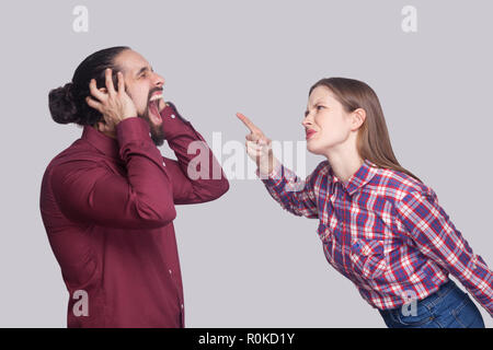 Profile side view portrait of angry woman standing and blaming at screaming unhappy man with black collected hair. indoor studio shot, isolated on gra - Stock Photo