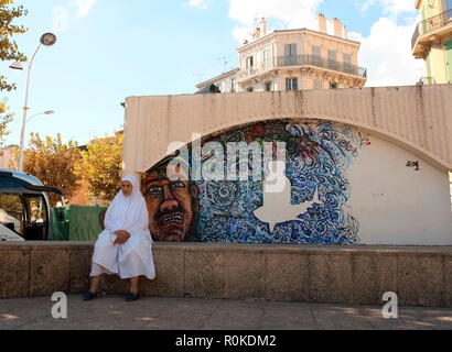 AJAXNETPHOTO. 2018. CANNES, FRANCE. - WOMAN SITS IN THE SHADE NEXT TO STREET ART PAINTED ON A WALL NEAR THE TOWN HALL. PHOTO:JONATHAN EASTLAND/AJAX REF:GXR180310_658 - Stock Photo