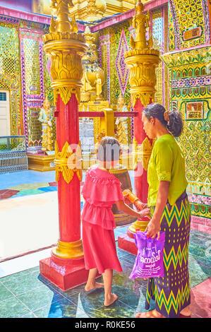 MANDALAY, MYANMAR - FEBRUARY 23, 2018: Buddhist devotee during the ritual of ringing the bell in Su Taung Pyae Pagoda, on February 23 in Mandalay. - Stock Photo