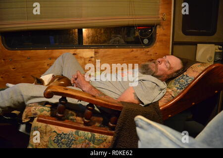 Man sleeping in a recliner with his dog. - Stock Photo