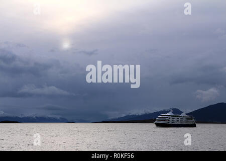 Cruise ship departs Port of Ushuaia along the Straits of Magellan under a stormy sky in early evening, Tierra del Fuego, Argentina - Stock Photo
