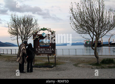 Couple reading the marker of the end of the earth (fin del mundo), Ushuaia, Argentina - Stock Photo