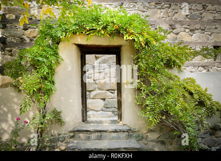 Wooden door frame gate covered with trees in front of stone retaining wall outside the Shigar fort. Skardu, Baltistan, Pakistan. - Stock Photo