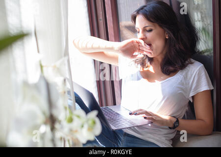 Attractive young woman working on a laptop computer on a sunny window seat feeling tired and yawning - Stock Photo