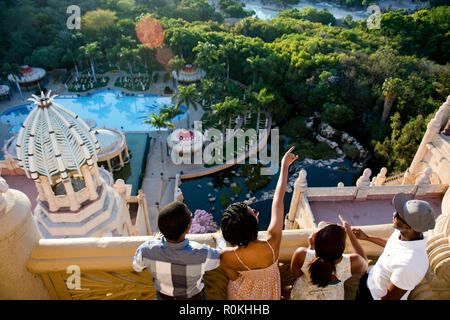 Group looking out over Sun City from a balcony in the Palace Hotel - Stock Photo