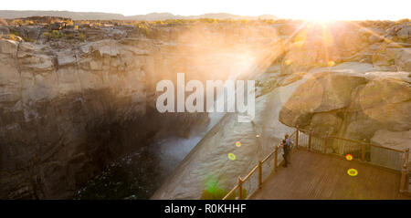 People standing by the Augrabies waterfall at sunset - Stock Photo