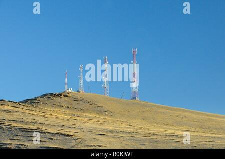 Autumn landscape with a telecommunication towers on top of a hill covered with dry yellow grass in Khakassia - Stock Photo