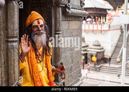 A Sadhu sits in one of the temples at the Pashupatinath temple complex, Kathmandu, Nepal - Stock Photo